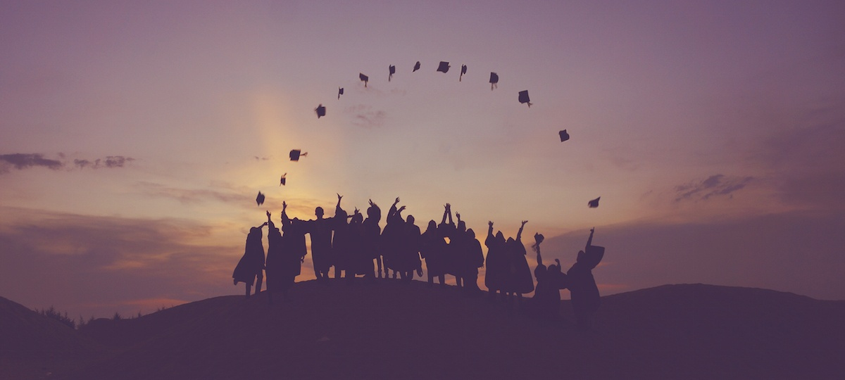 College graduates throwing mortarboards in the air